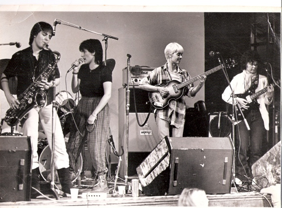 PMT in performance, saxophonist, singer holding microphone and looking at the drummer at back of stage, bass guitarist smiling, guitarist looking seriously at her guitar. All have microphones and there are a lot of amplifiers on stage.