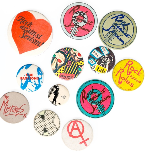 A collection of bright Rock Against Sexism badges, using anarcha-feminist symbol and slogans such as 'rock against roles' and 'rock against sexism, and names of bands The Passions, X-Ray Spex, the Mistakes.