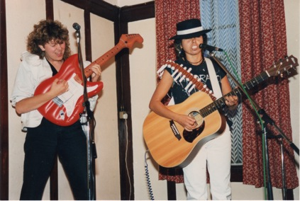 Julie McNamara and Judy Coutinho performing. Julie plays an inflatable toy electric guitar with great gusto, and Judy, who is playing a real acoustic guitar, wears a cowboy hat and has a bandelero in the style of a bullet holder made of tampaxes slung over her shoulder.