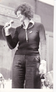 Black and white photo of Ruthie, smiling and singing into a hand held microphone.