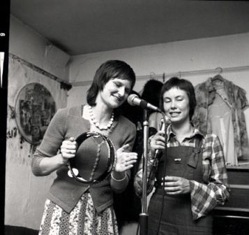 Two women in rehearsal. Ruthie plays the tambourine and uses a microphone on a stand, and Caroline sings into a hand held mike. Both are clearly enjoying themselves.