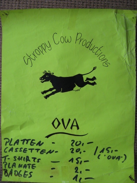A poster with green background, black letters, Stroppy Cow Productions logo of a dancing cow, and a list of items of merchandise, t-shirts, badges, cassettes, in German.