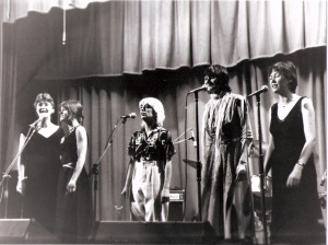 Five women singers on stage with microphones and amplifiers, dressed in dresses and smart trousers.