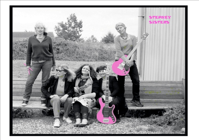 Cover of the CD is a black and white photo of the women from the Stepney Sisters, with bass, drumsticks and guitar and their name picked out in bright pink. The 5 women and their instruments are sitting or standing on a wooden bench in an outdoor location, trees and a barn in the background.