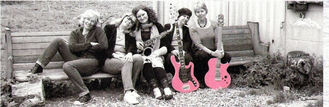 The five Stepney Sisters in 2011, all seated on a long wooden bench, with their instruments, leaning against one another affectionately and smiling. The bass and guitar are picked out in bright pink.