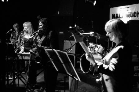 A photo of the reunited band, on stage playing guitar, singing, keyboards, and bass, the drum kit at the back of the stage and music stands, microphones and amplifiers also.
