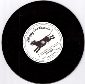 A photo of the E.P. record Stereotyping, with the name Stroppy Cow Records hand written and the label's logo of a cartoon of a happy, dancing cow in black on white background. Track titles Stereotyping and Song About Myself are also printed on the label.
