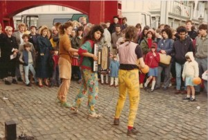 Colour action photo of the band playing on the street. An audience watches as they play.