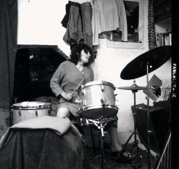 Suzy in rehearsal, playing her drum kit. The rehearsal is in a room in  a house, clothes and curtains can be seen hanging in the background.