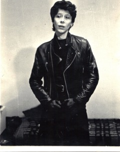 Nina Rapi, black and white photo, in black leather jacket looking serious.