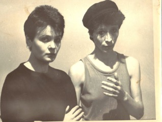 Black and white photo: pauline Channing in black t-shirt, Nina Rapi in vest and cap, looking serious, holding hands in front of their chests.