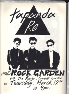 The three band members, dressed in black and white shirts and braces, dark sunglasses, with a large black triangle above them, advertising a gig at the Rock Garden.