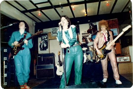 On a small stage in a pub, the band is fronted by guitarist, singre and bassist, with drummer at the back. A colour photo showing the women dressed in shiny blue and pink cat-suits.
