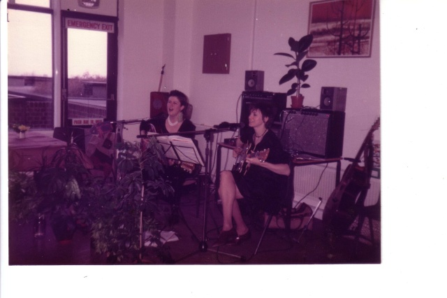 Colour photo of Rosemary and Jana playing at a tea dance in an older people's home, from the audience's point of view. Both play guitars and sing from lyrics on a music stand, near to hand is other equipment such as guitars, percussion instruments.