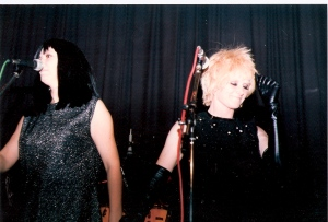 Two singers on stage in Islington Town Hall with microphones, dressed in 1960s clothes, lurex dresses, long wig, black gloves. Colour shot taken from audience.