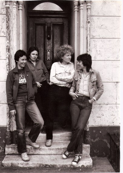 A posed black and white publicity shot of The Harpies standing in the doorway of the front of an old house, possibly a London squat, two grinning at each other, two looking out, wearing jeans and denim jackets and shirts.