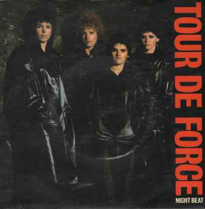 Colour photo of the band, all dressed in black leather on a black back ground. Stern expressions, looking confidently at the camera. 'Tour de Force' written in bold red letters down the right hand margin.