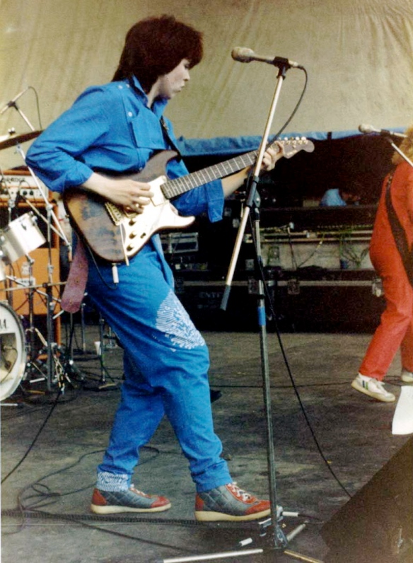 A dynamic photo of Deidre playing lead electric guitar, stepping forward dramatically, behind a microphone. Drumkit and bass player partly in shot.