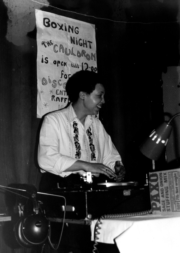 Terri Quaye in DJ mode at her Cauldron Women's Disco, working turntables, a hand-painted poster advertising the Boxing Night event and raffle on the wall behind.
