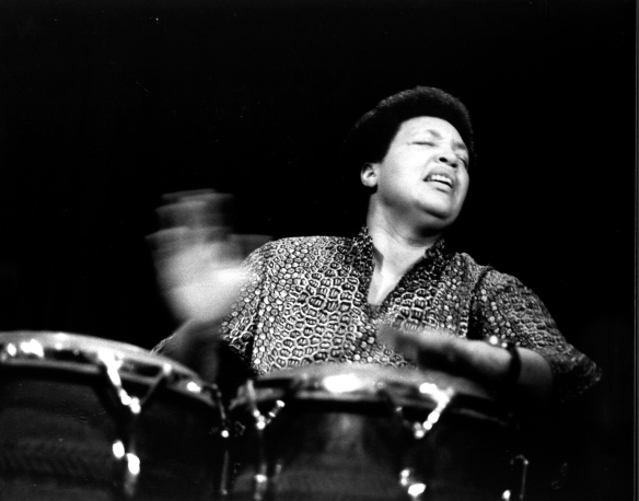 Terri Quaye playing a solo concert on conga drums, hands blurred with speed.
