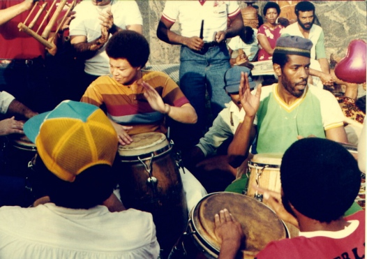 Terry Quaye and several African-American drummers playing congas in Washington Square, New York. Other people in background playing hand percussion.