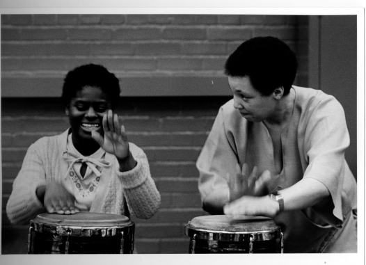 Terri Quaye and a young woman student playing conga drums in a workshop for disability charity Scope, 1983