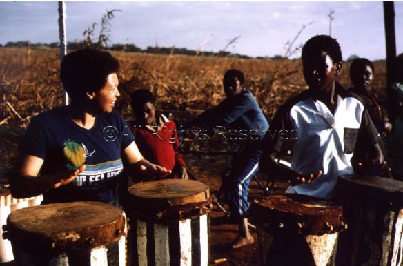 Terri playing conga drums with other musicians, outdoors in Zimbabwe.