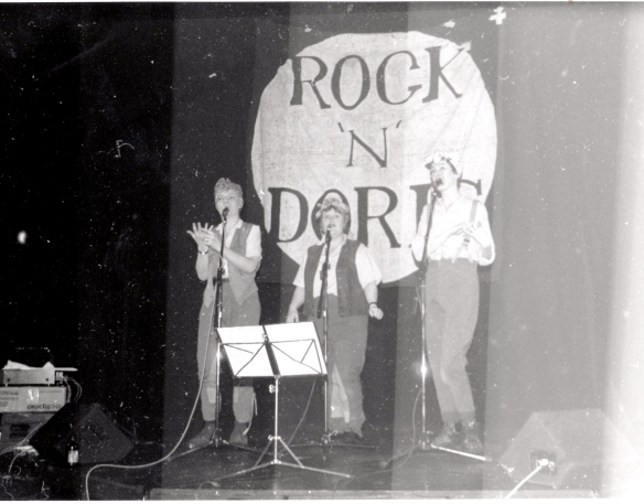 A trio of women in an old black and white photo, onstage with microphones, singing, one signing. A large banner in background saying 'Rock 'n' Doris'.