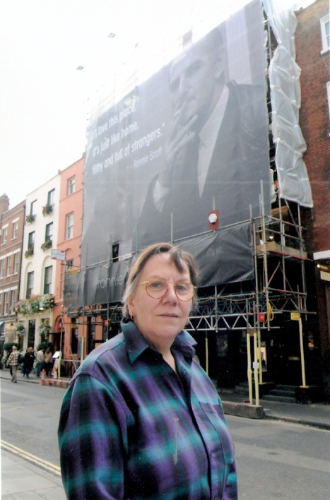 Val Wilmer stands in street in Soho, with a very large banner on the club's outside wall behind her showing founder Ronnie Scott laconically smoking, smiling.