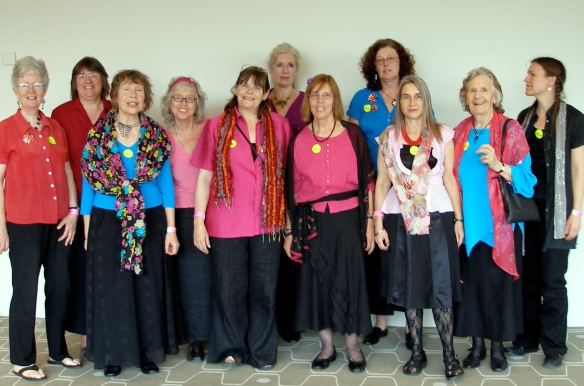 The eleven woman line-up of the choir, dressed brightly in pinks and blues and all smiling.