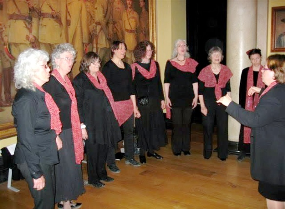 Eight women all dressed in black wearing red scarves, singing and focusing on their conductor at the front. They are performing in a smart large room decorated with paintings.