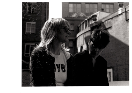 Vick and Barbara talking outside at the back of a row of houses.