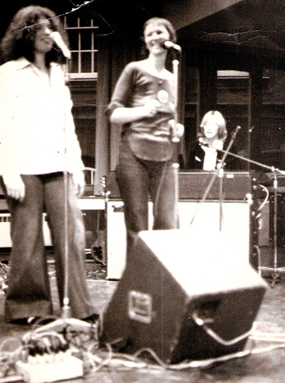 Black and white photograph of Vicky Scrivener (singing), MaggieNicols (singing), Josie Mitten (playing keyboards) performing. Vicky and Maggie smile at each other.