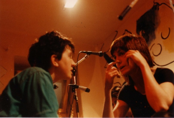 Colour photo of  Viv Acious, Ova sound engineer 1983-1985 and Rosemary in Germany 1983. The pair look at each other away from the direct gaze of the camera and are having a serious conversation amidst microphones.