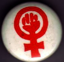 A photograph of the WLM badge, red fist in women's symbol on white background