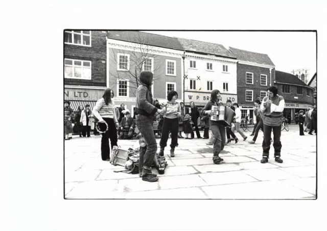 Black and white photograph of the York Street band playing in a town square in York. People are gathered to watch in front of shops and the women play tambourine, accordian, flute and percussion.