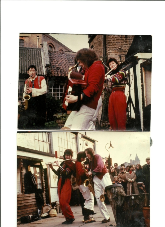 Colour photo of York Street Band playing outdoors, in a city square. Saxophone and flute players watch the accordionist. Image indicates that the band wore complementary red clothes when they performed. A small crowd is gathered to watch.