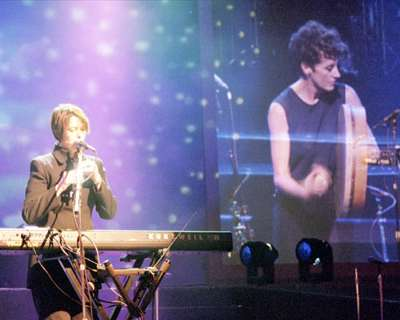 Live colour photograph of Zrazy performing, with bright blue stage lighting. Carole plays flute while standing behind electric keyboards and microphone, Maria at the front plays a bodhran, the Irish hand drum.