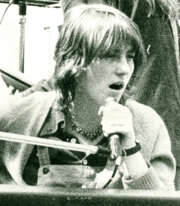 photo from 1977 of Josie Mitten singing into microphone and playing keyboard at a Jam Today gig