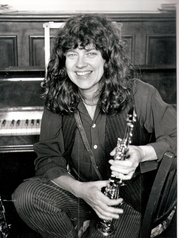 A black and white photo of Lindsay Cooper seated in front of a piano, holding her bassoon, smiling.