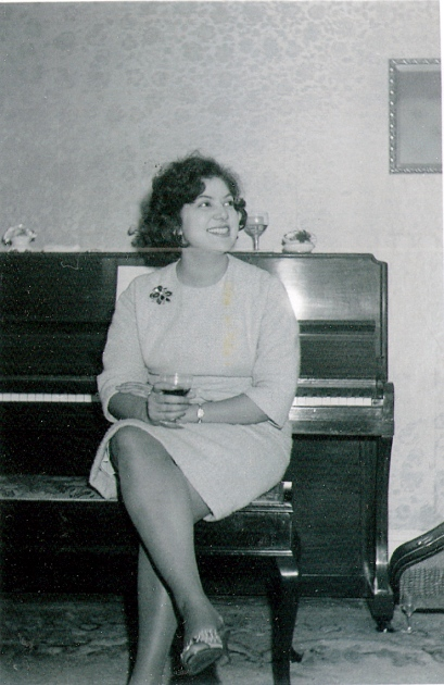 black and white photo of Ramona Swale smiling, seated by piano and holding a glass of wine.
