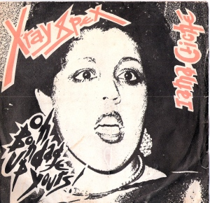 cover of Xray Spex record shows Poly Styrene's face while singing, and titles of songs 'Oh bondage, up yours' and 'I am a cliche.'