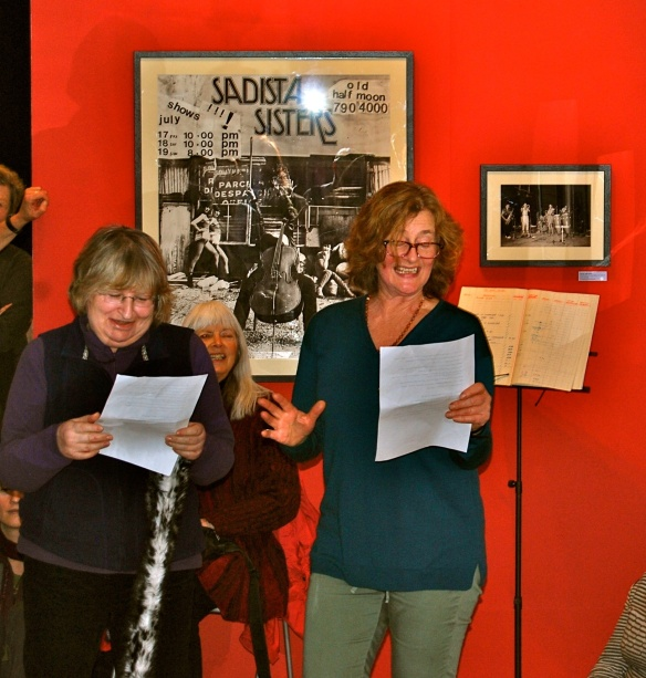 Two women standing facing the camera, holding pieces of paper and singing. Frankie Armstrong is in the background of the image smiling.