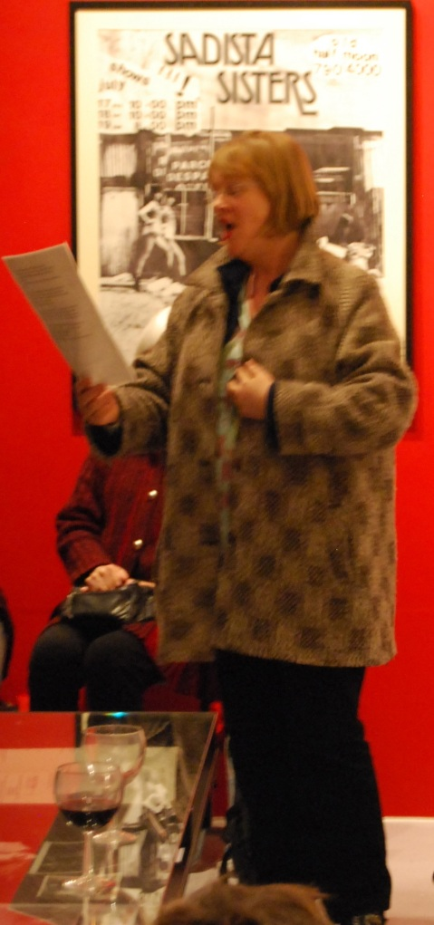 Lizzy is pictured singing emphatically, reading the words from a sheet of paper