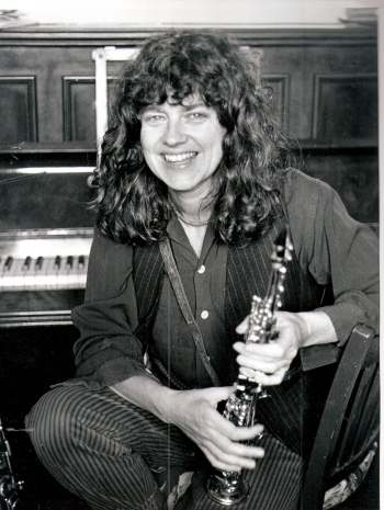 A portrait of Lindsay Cooper smiling, holding her sax, in front of a piano.