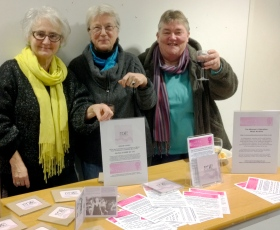 Three women smiling behind a stall displaying CDs, WLMA leaflets and posters, smiling and raising glass.