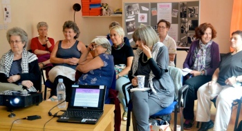 A group of women enjoying a workshop discussion; display board of  WLMA items in background.