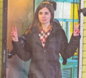 One of the three women from Russian punk feminist group Pussy Riot jailed by Putin  emergs from  prison giving victory signs.